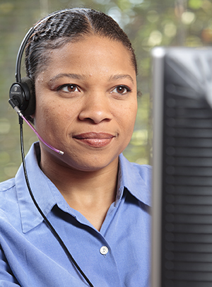 Woman at computer wearing telephone headset.