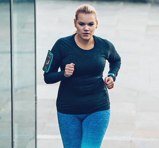 Young overweight woman jogging outdoors