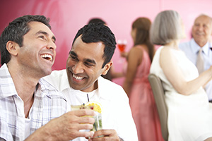 Two men having drinks and laughing at a party.