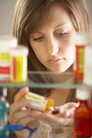 Young woman pouring out pills, view through medicine cabinet.